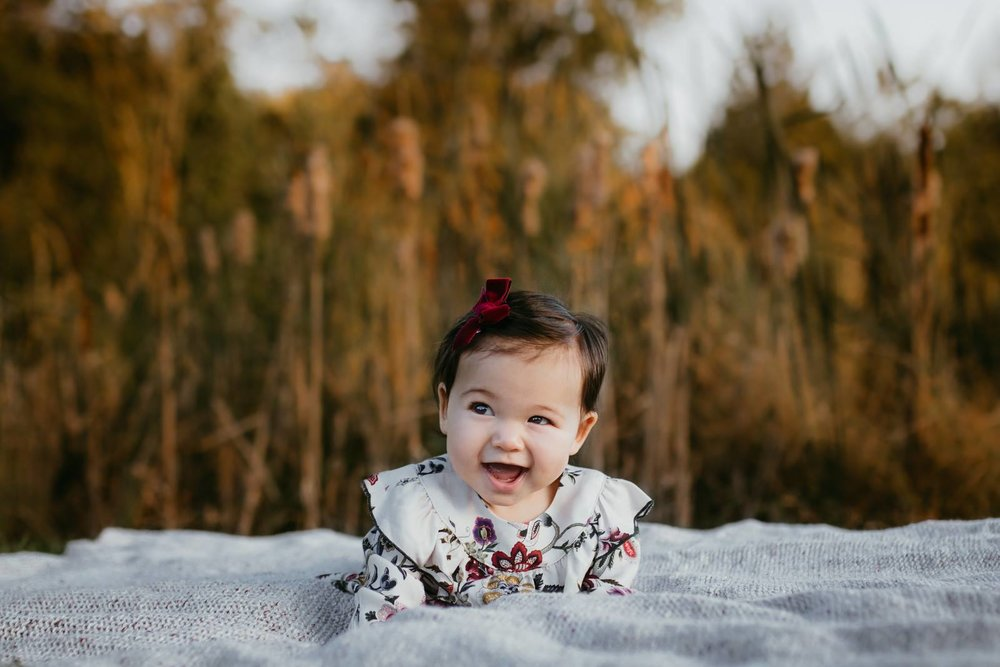 Portrait of a six month old girl in a floral dress laying on a blanket in a field at Clyde's in Broadlands VA.