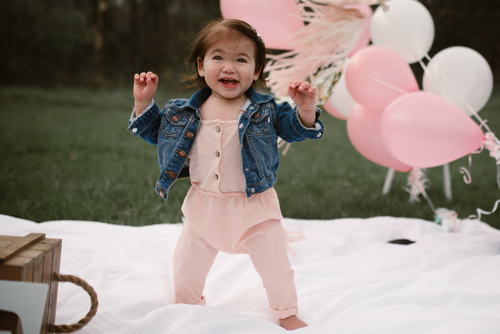 Portrait of a one year old girl in a pink romper and jean jacket standing with balloons behind her at Red Rock Overlook in Leesburg, VA