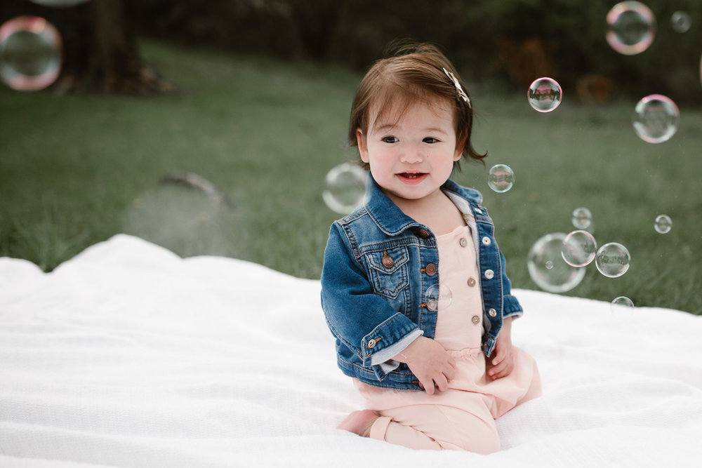 Toddler in a pink romper and jean jacket sitting on a blanket surrounded by bubbles at Red Rock Overlook in Leesburg, VA