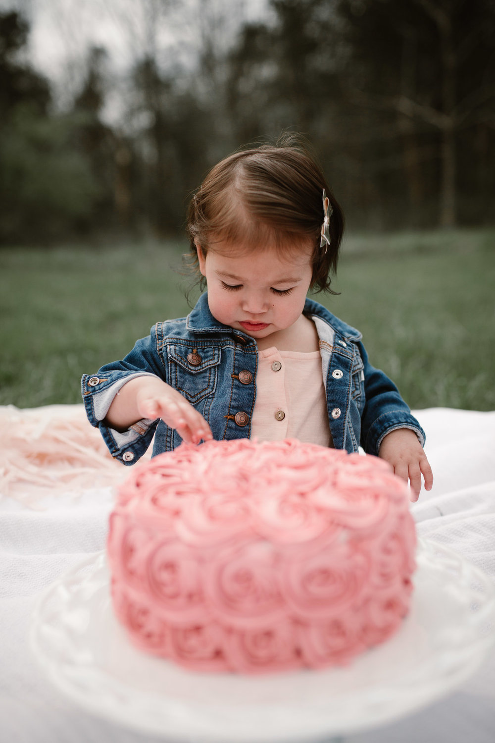 Toddler girl in a jean jacket examines her pink birthday cake at Red Rock Overlook in Leesburg, VA