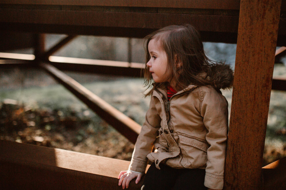 Girl in a brown coat sits under a rust colored bridge and looks off in the distance in Ashburn, Virginia