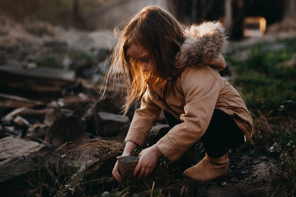 Girl in a brown coat kneels down near a creek and plays with a rock in Ashburn, Virginia