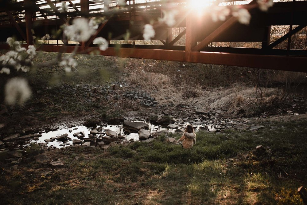 Girl sits under a bridge near a creek as the sun sets in front of her in in Ashburn, Virginia