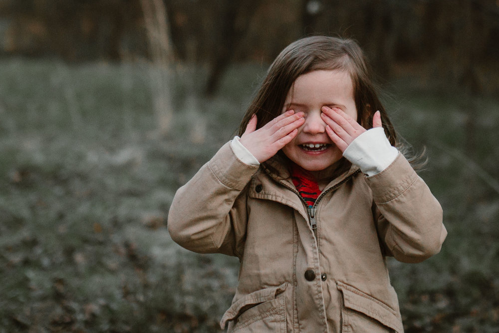 Toddler in a brown coat stands with her hands over her eyes and a big smile in Ashburn, Virginia