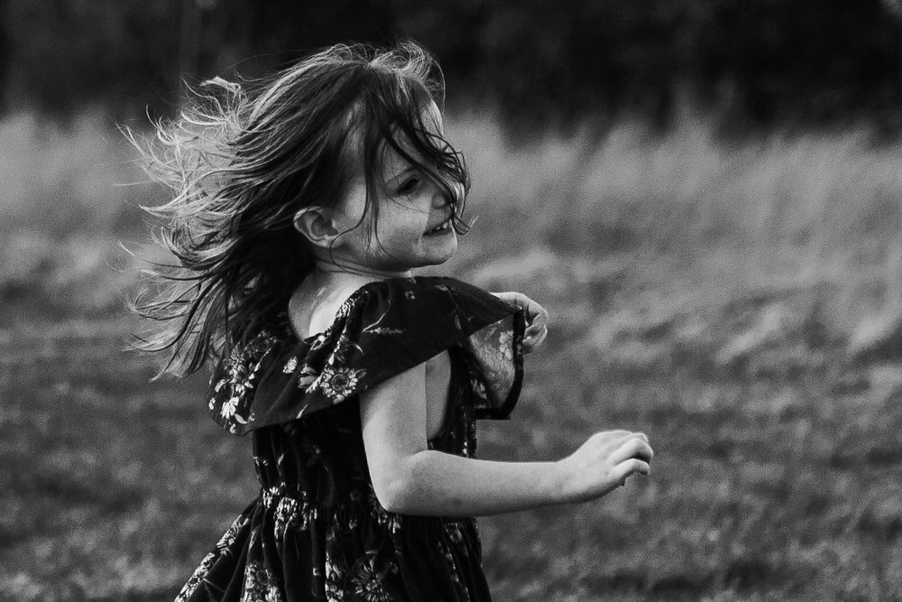 Black and white; girl in a floral dress twirls in a circle with her hair flying in her face in Ashburn, Virginia