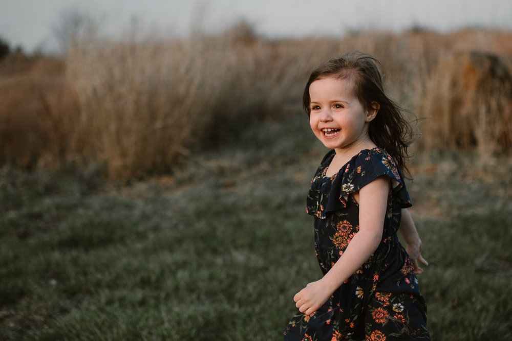 toddler in a floral dress runs through a field and laughs in Ashburn, Virginia