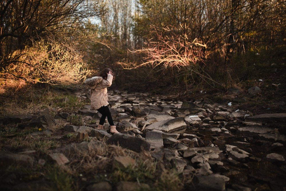 Toddler in a brown coat tentatively steps on a rock as she tries to cross the creek in Ashburn, Virginia