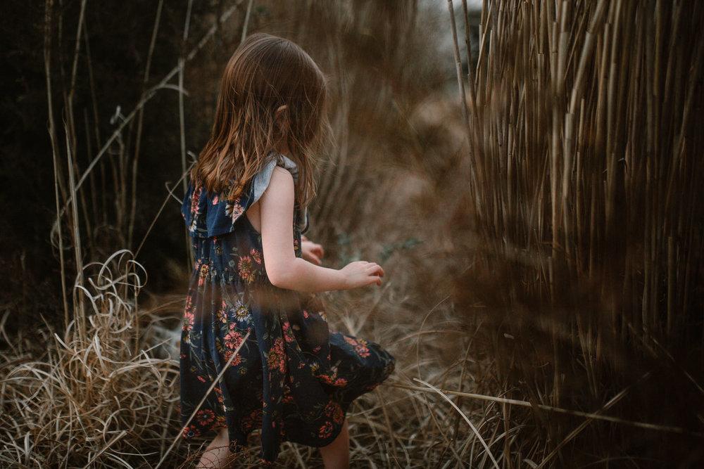 toddler in a floral dress walks through tall grass in Ashburn, Virginia