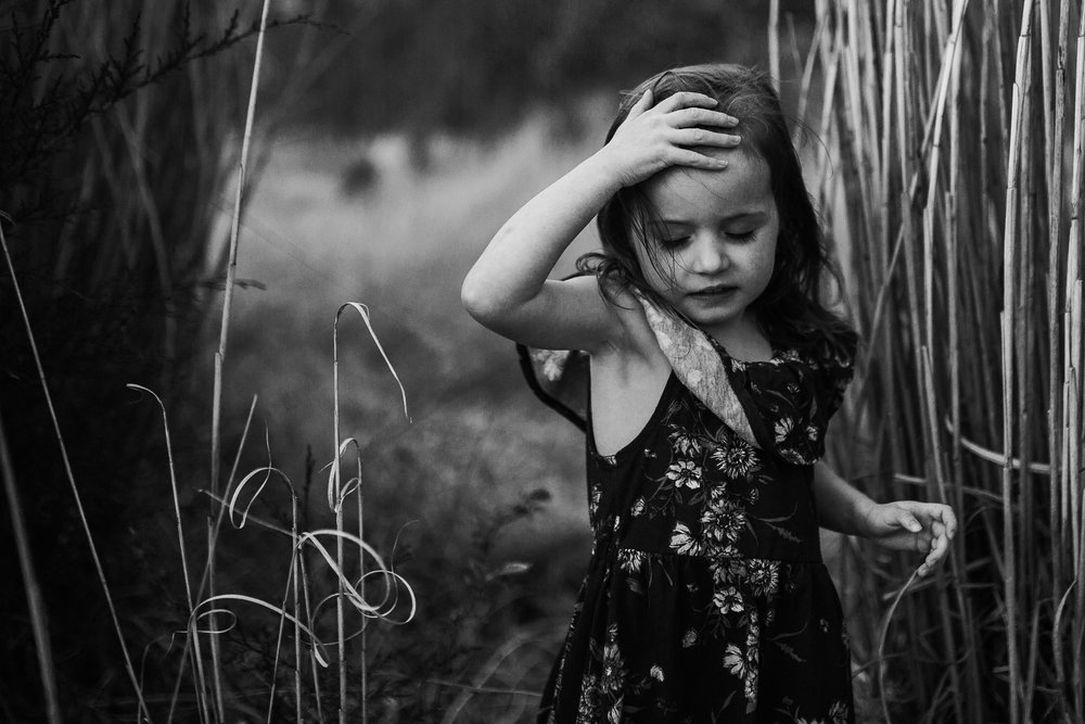 Black and white; toddler in a floral dress walks through tall curly grass and pushes hair from her face in Ashburn, Virginia