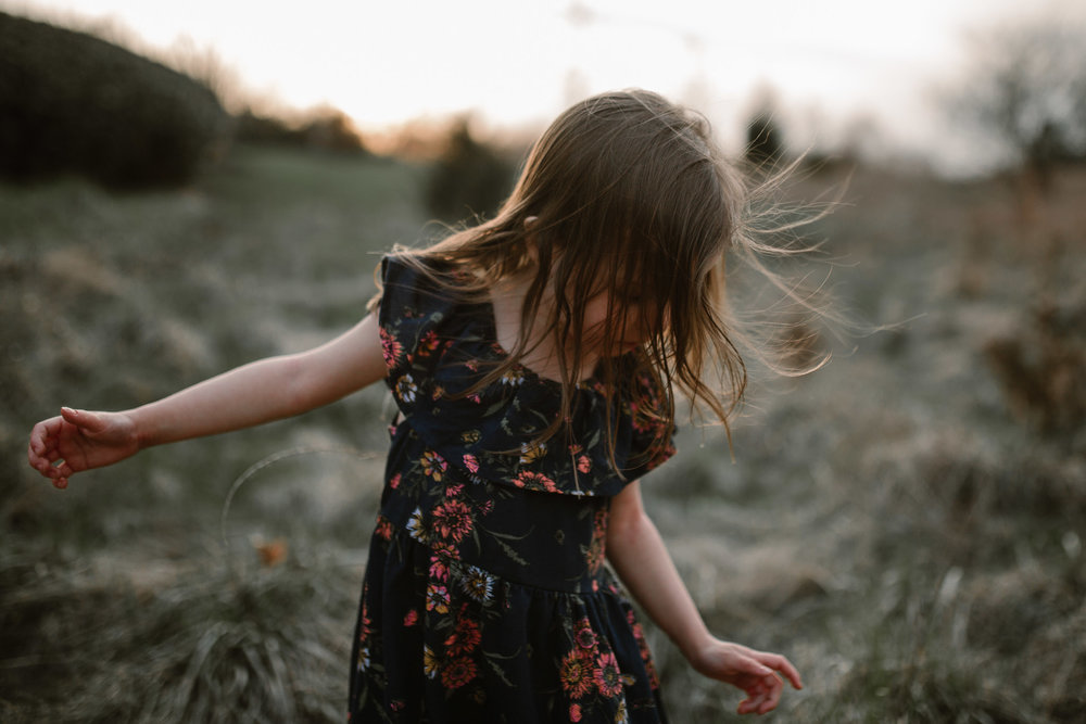 Young girl in a dark blue dress twirls in a field with her hair in her face in Ashburn, Virginia