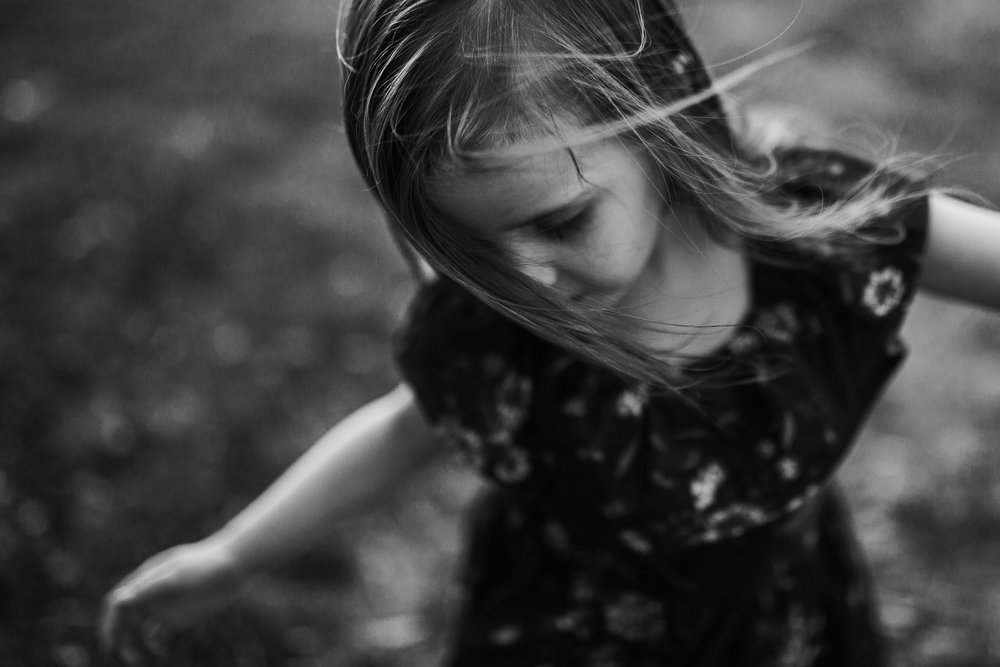 Black and white; young girl spreads her arms wide as the wind blows her hair into her face in Ashburn, Virginia
