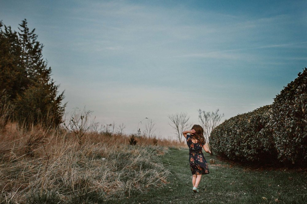 Young girl in a navy dress walks through a field with her hand in her hair in Ashburn, Virginia