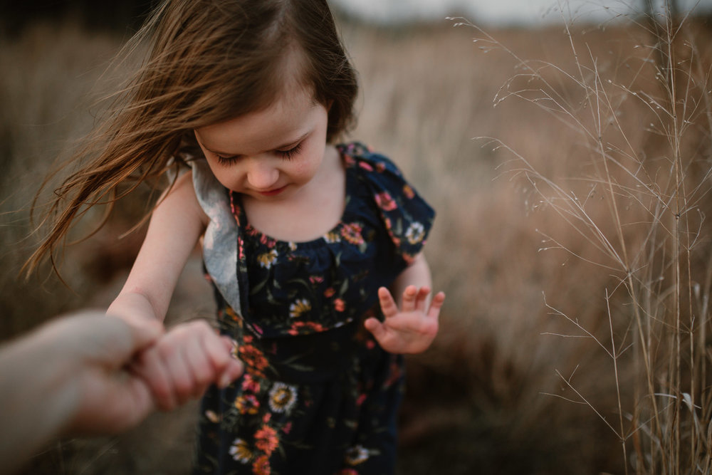 Girl in a floral dress holding someones hand off camera as she looks down at the ground in Ashburn, Virginia