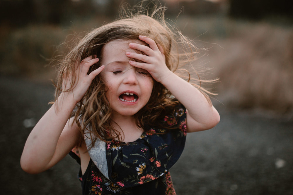 Toddler in a blue floral dress cries out in frustration as she tries to keep her hair out of her face during high winds in Ashburn, Virginia