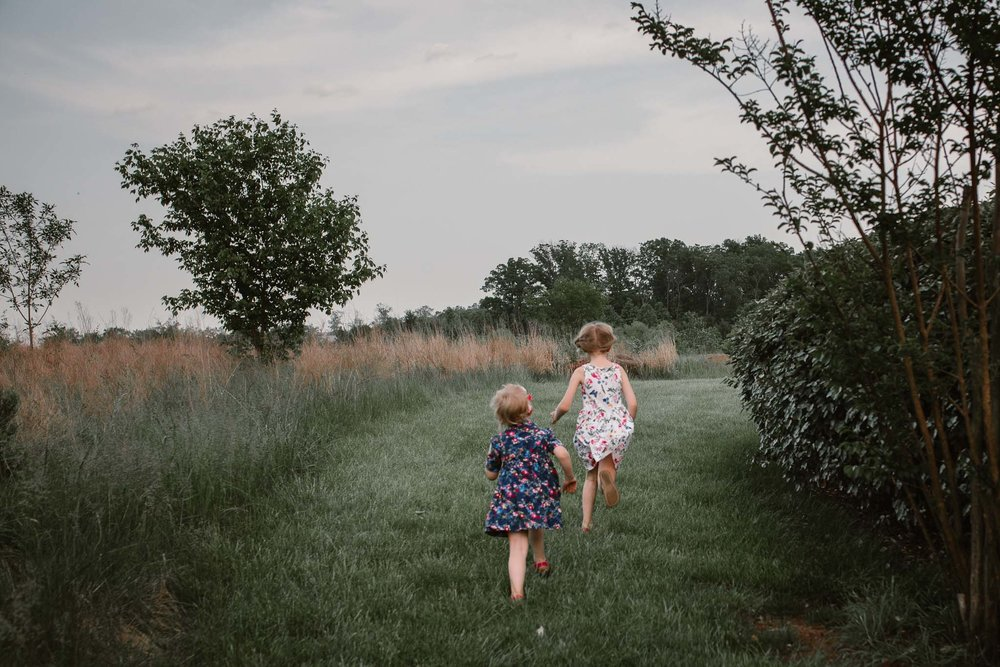 Two sisters race away through a field  at Beaverdam Run in Ashburn, Virginia