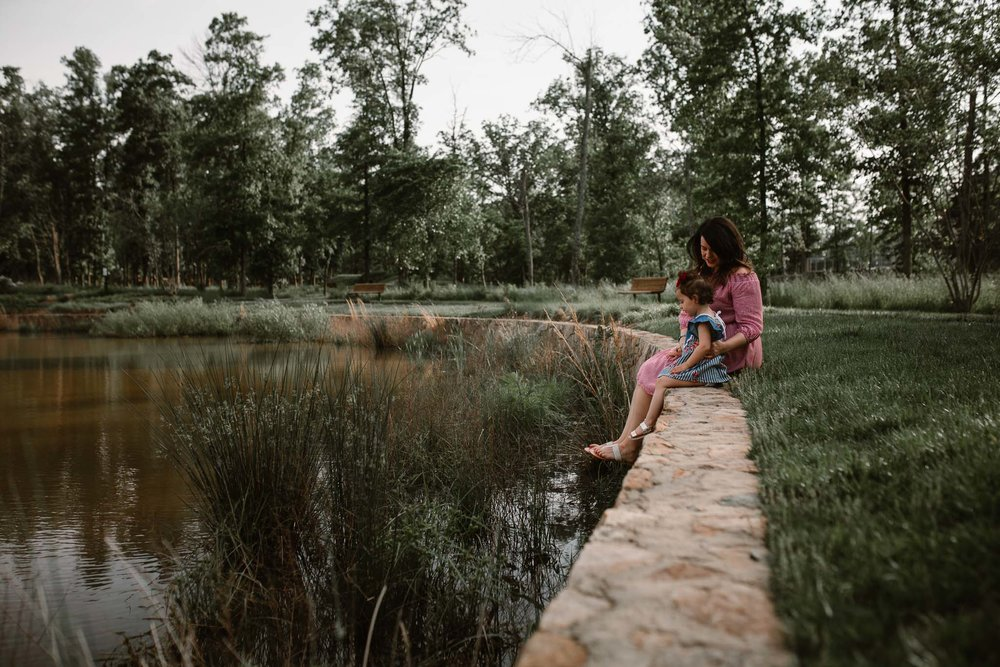 Mother and Daughter sit together near a lake at The Barn at One Loudoun in Ashburn Virginia
