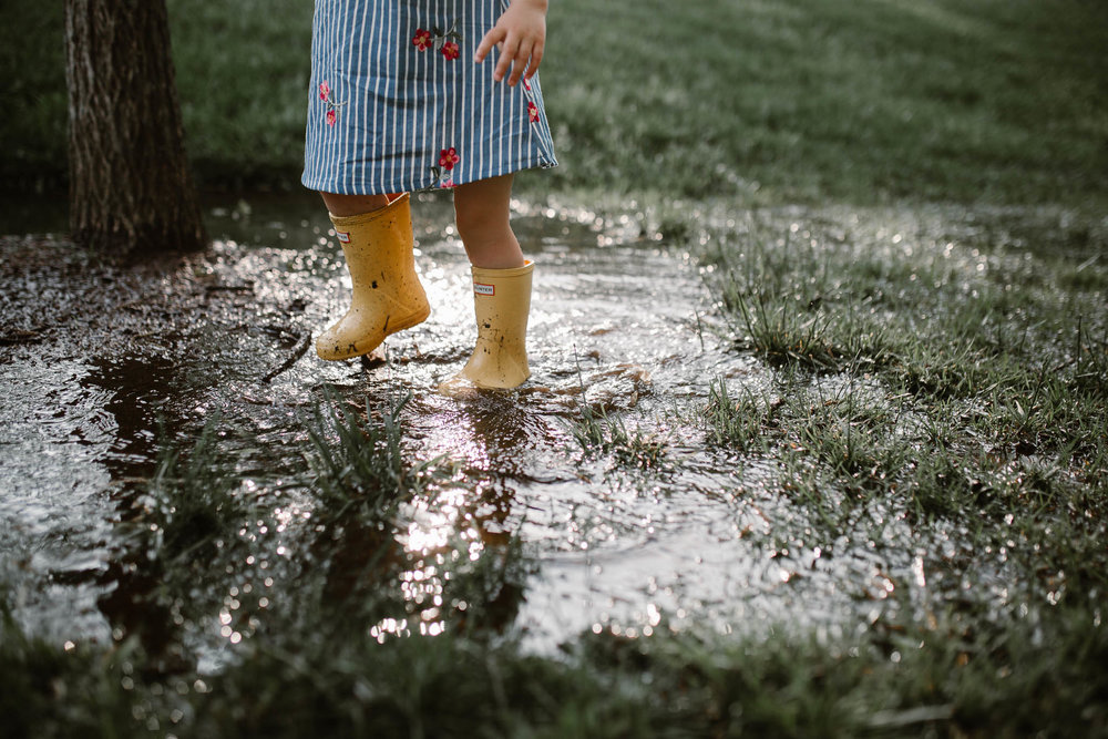 Close up of toddler in yellow Hunter boots splashing through a big puddleat The Barn at One Loudoun in Ashburn, Virginia