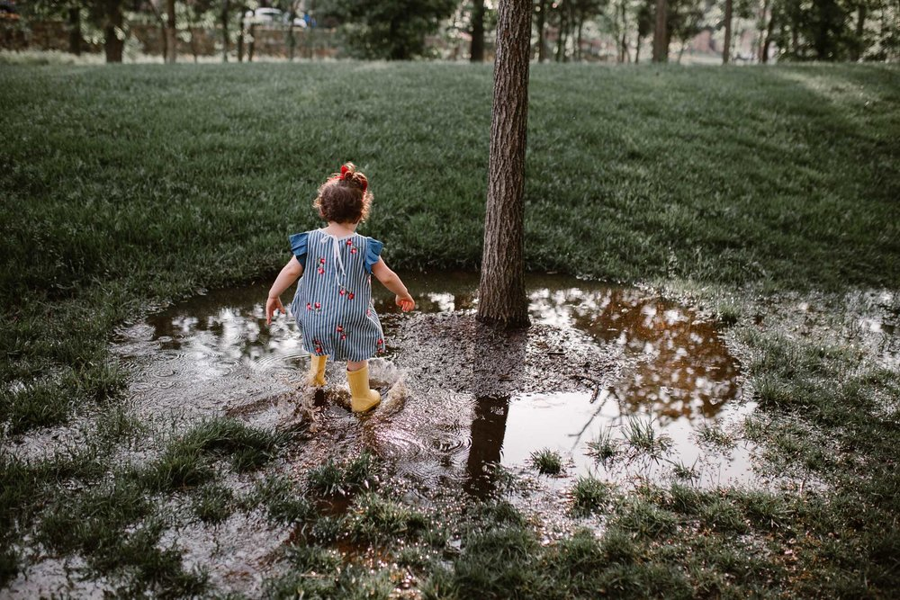 Toddler in yellow hunter boots jumps in puddles at The Barn at One Loudoun in Ashburn, Virginia