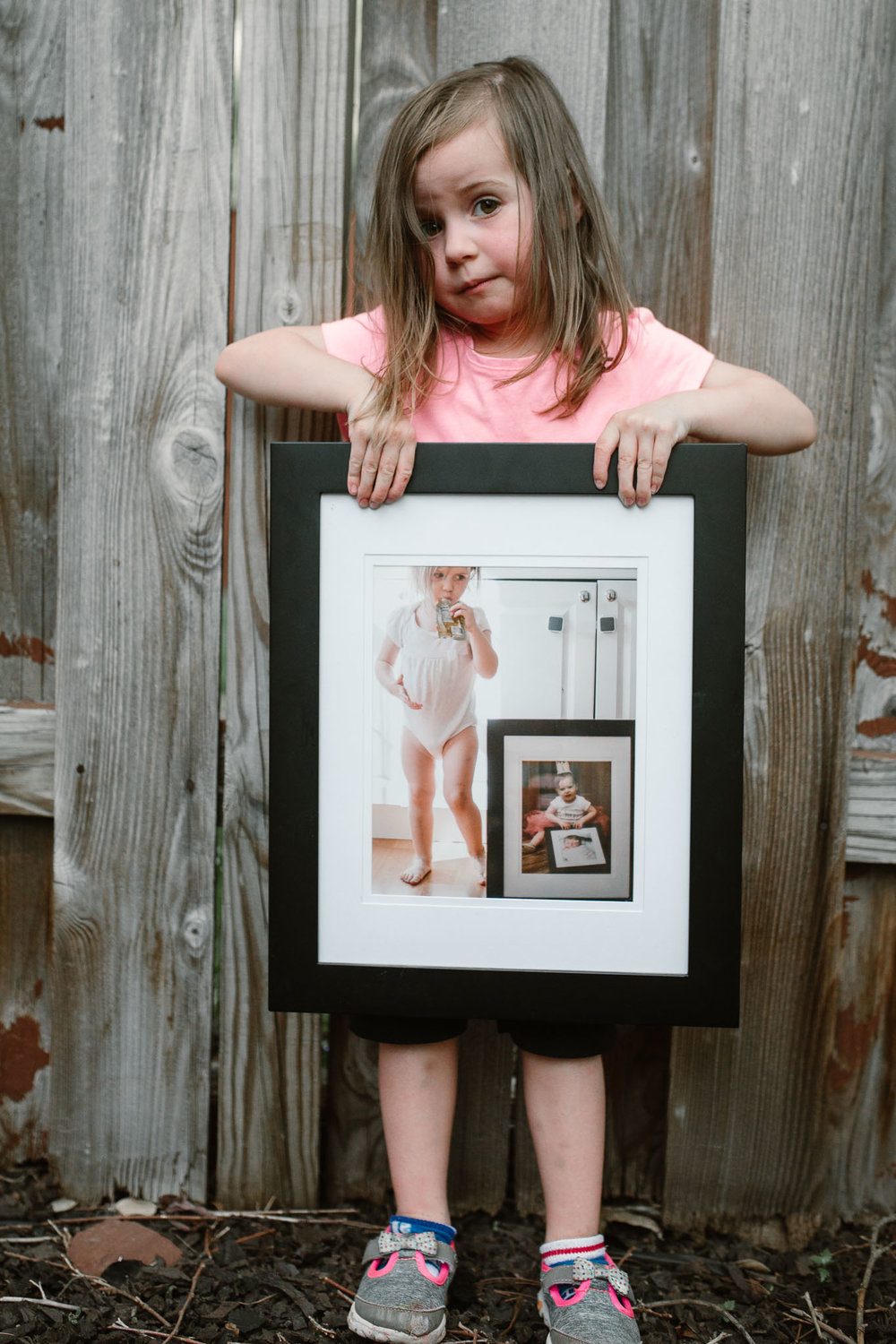toddler holding a frame with pictures of herself when younger lifestyle childhood family photography