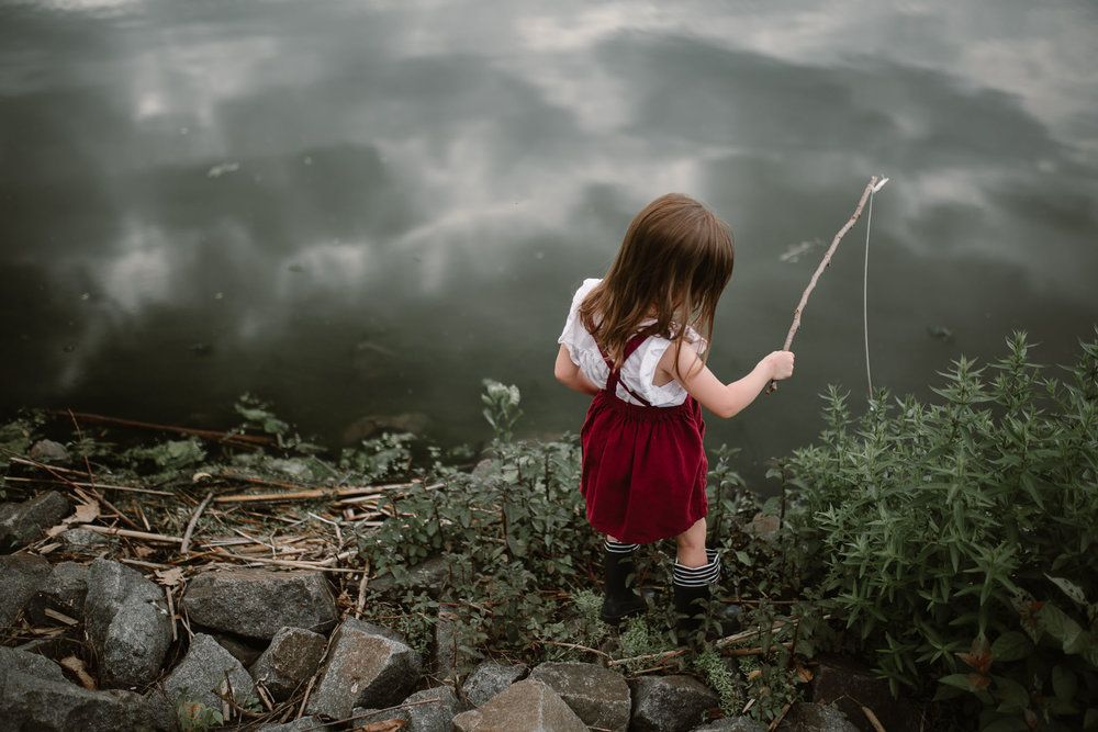 Toddler using a stick to fish in the lake at Ashburn Village virginia