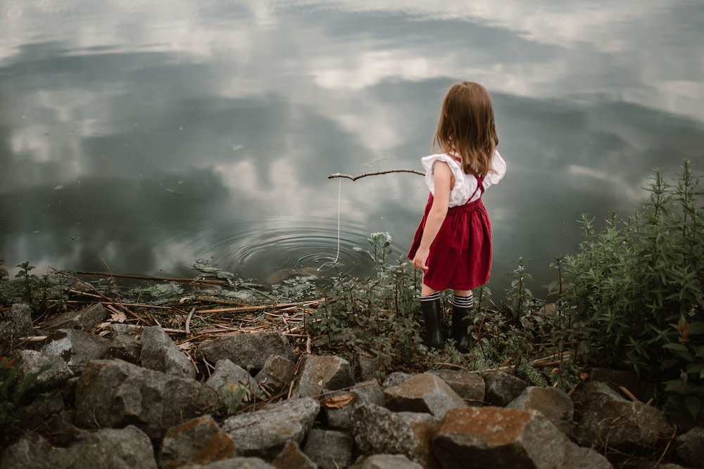 little girl using a stick and string to fish in ashburn village lake in northern virginia documentary family photography