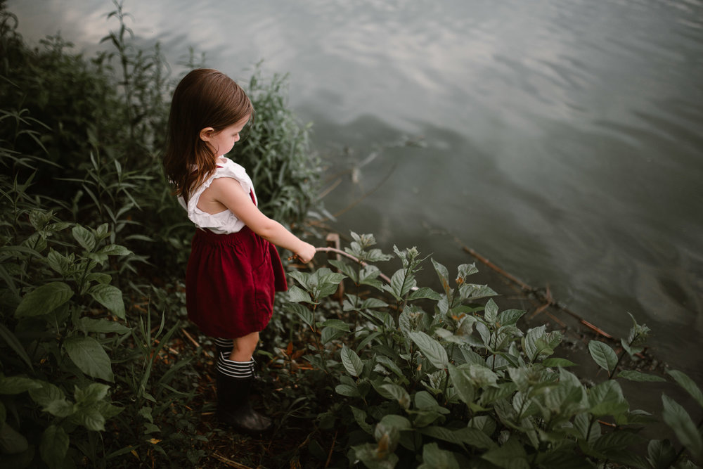 little girl in a red skirt fishing in Ashburn Village lake in northern virginia documentary childhood photography