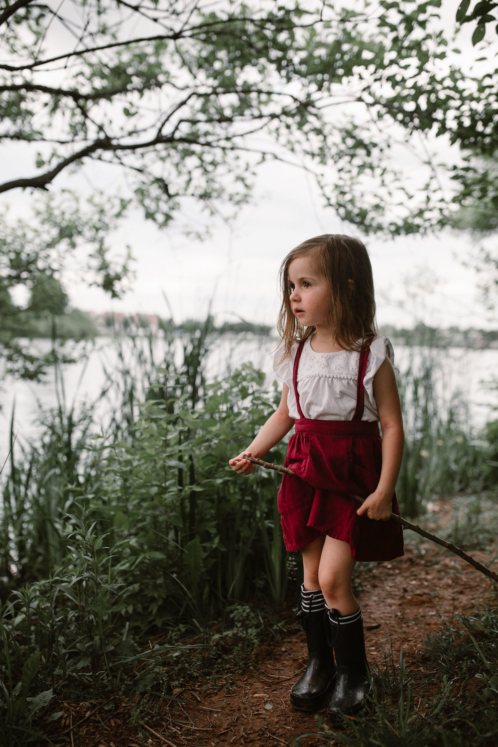 toddler in red overall skirt using a stick to fish at ashburn village lake in nothern virginia documentary childhood photography
