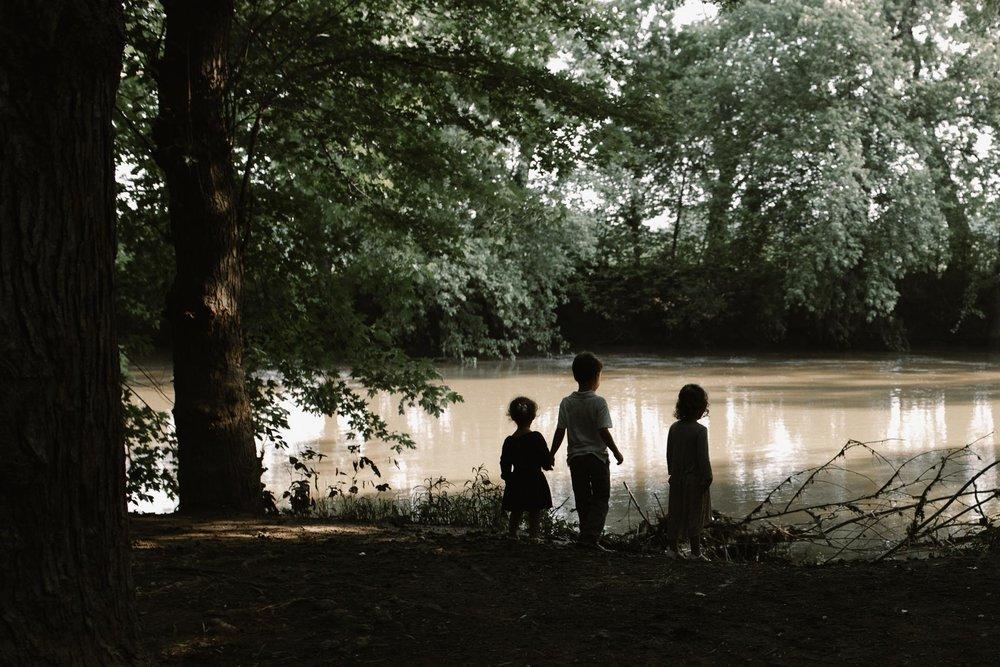 three siblings looking out at a muddy river  at Bles Park in Ashburn, Virginia