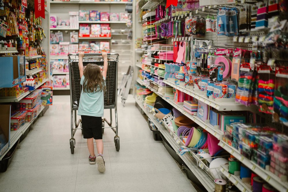 Girl in a blue dress pushes a shopping cart through a craft store