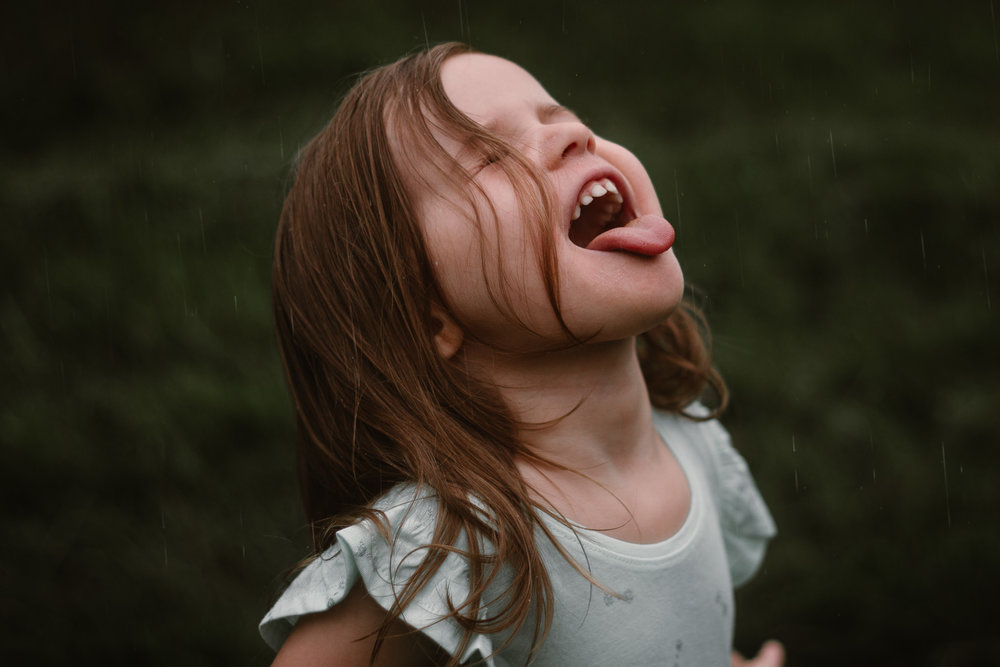 Girl in a blue dress stands in the rain and tries to catch raindrops on her tongue