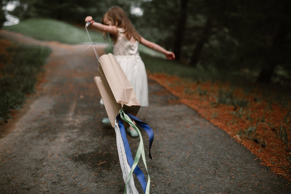 Girl in a white dress runs with a homemade kite trailing behind her