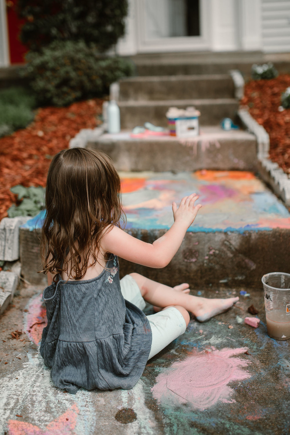 Girl colors with vibrant chalk on the sidewalk outside her home
