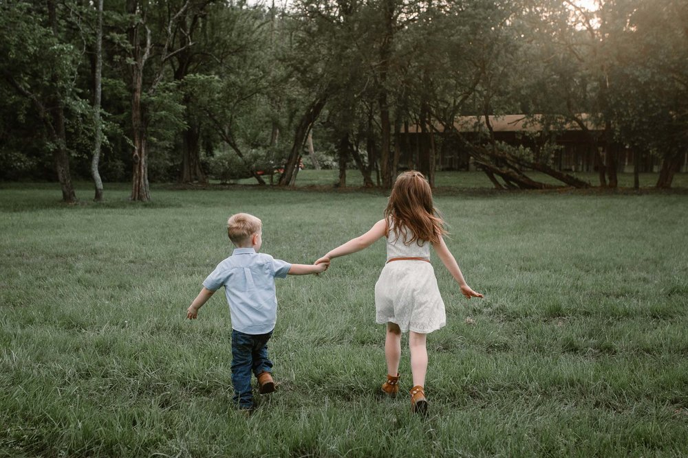 Boy and girl hold hands and run together at Morven Park in Leesburg, Virginia
