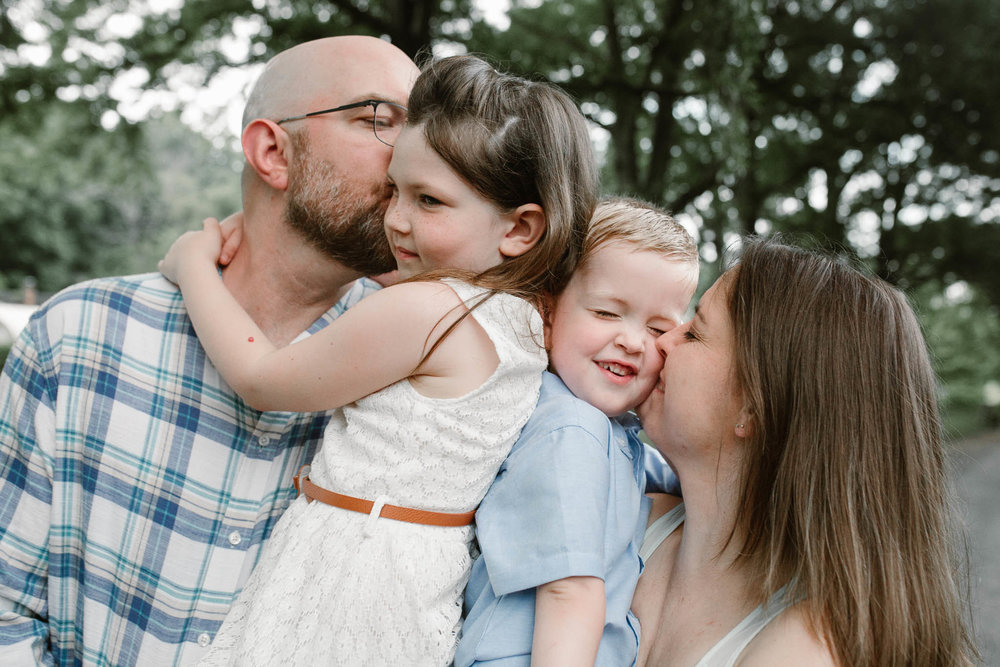 Family of four cuddle together and parents kiss kids at Morven Park in Leesburg, Virginia