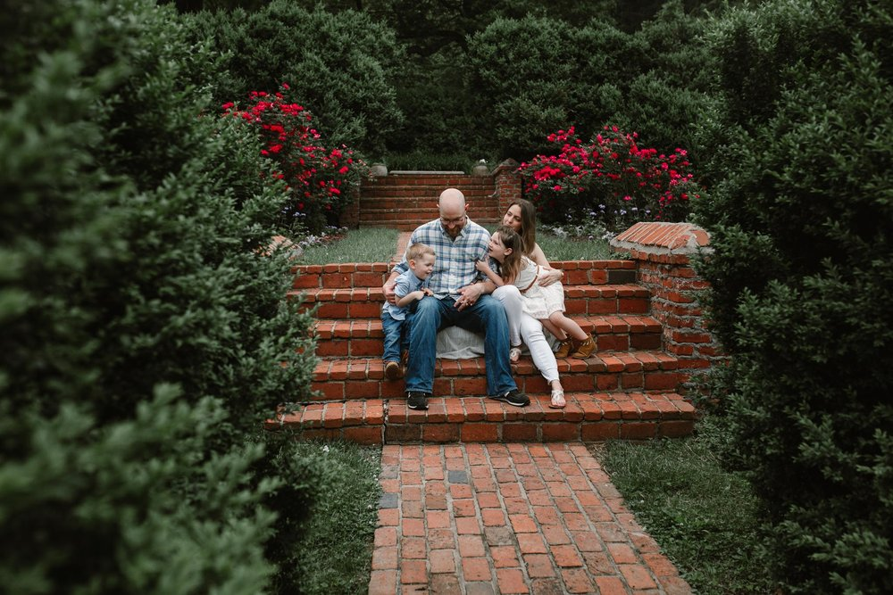 Family sits together on a brick staircaseat Morven Park in Leesburg, Virginia