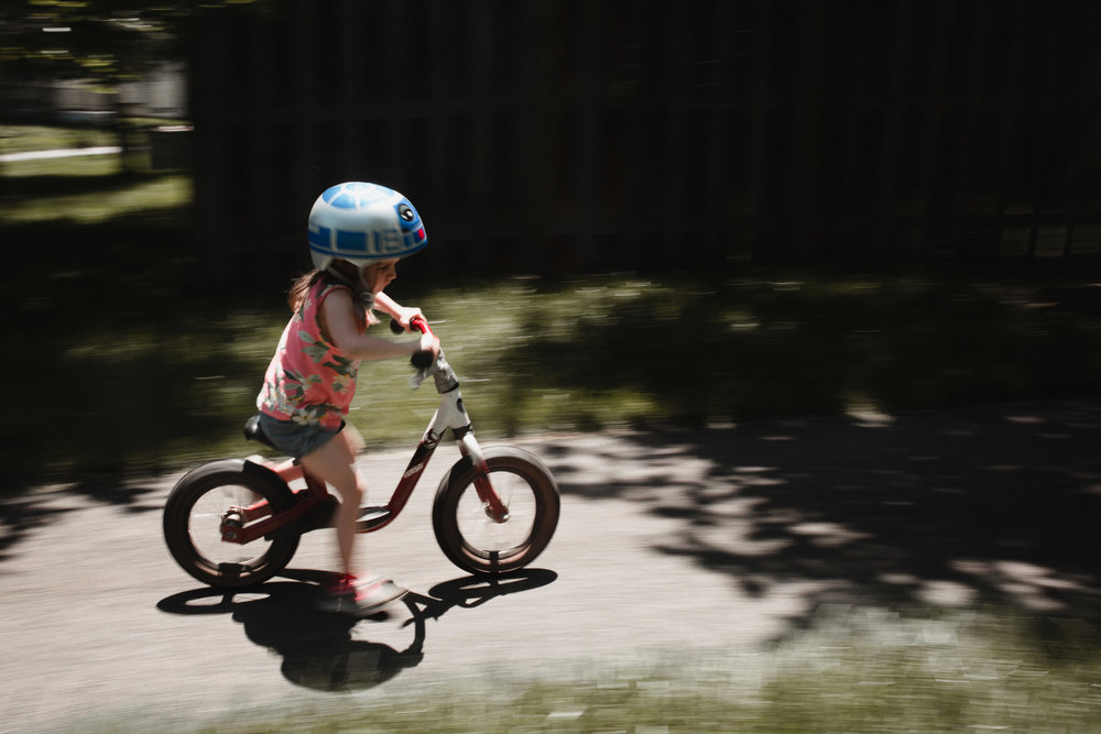 Panning image of a girl riding her bike