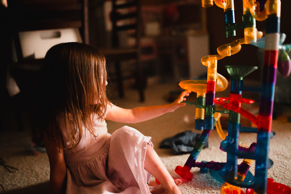 Girl playing with a multi-colored marble maze