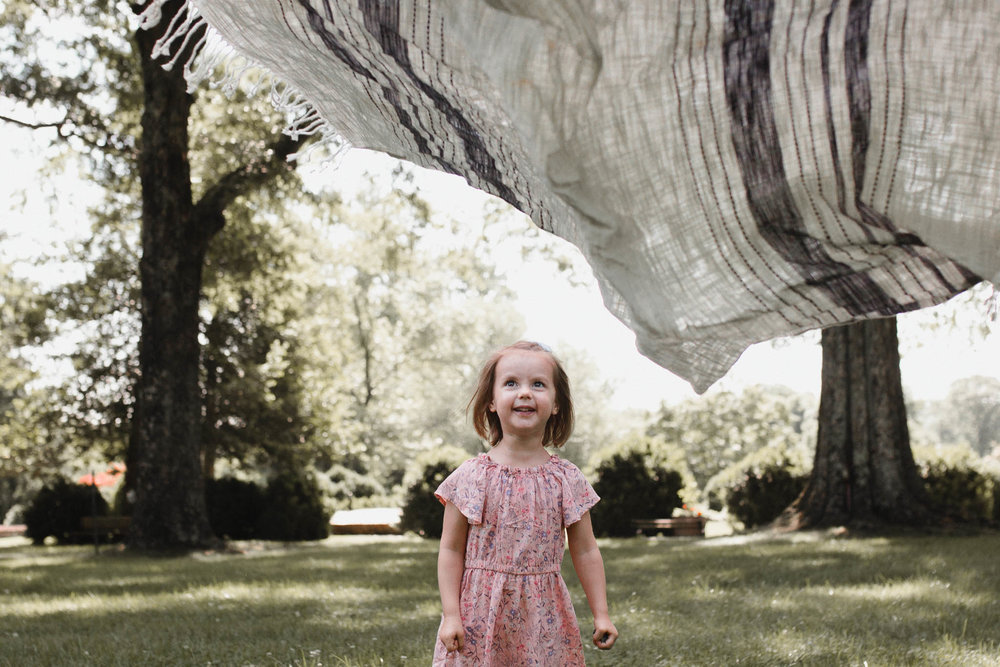 Girl stands under a blanket and grins before she runs under it at Morven Park in Leesburg, Virginia
