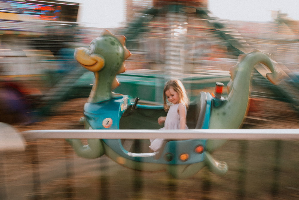 Panning image of a girl at a carnival in a dinosaur ride at One Loudoun Carnival in Ashburn, Virginia