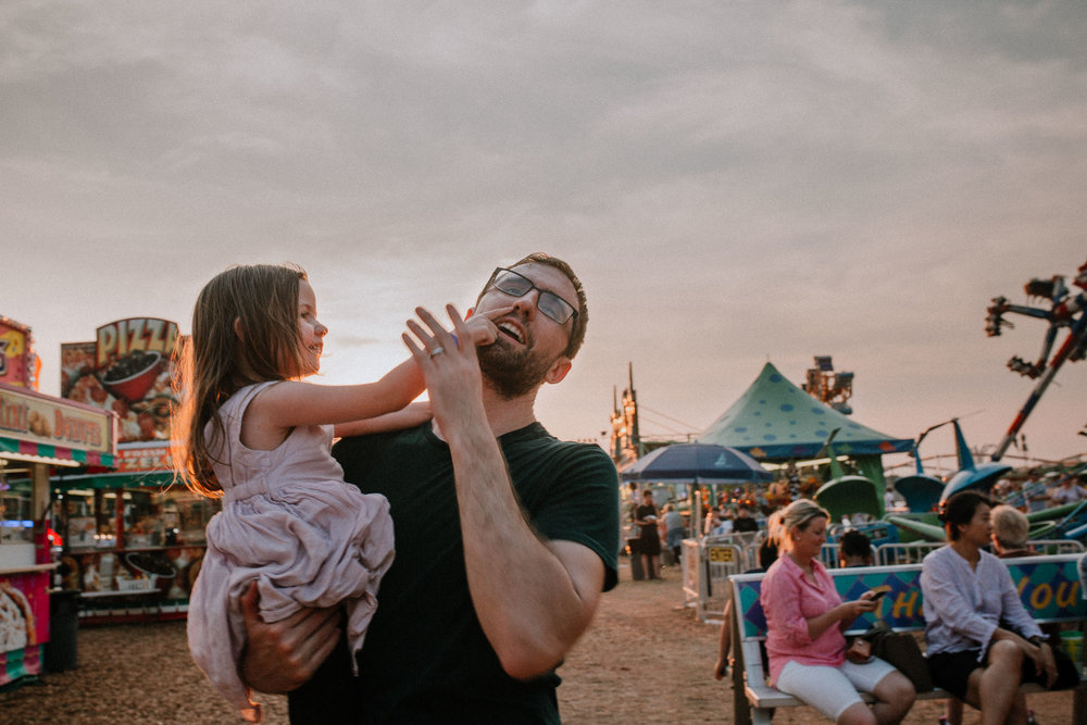 Father holding daughter at the One Loudoun Carnival in Ashburn, Virginia