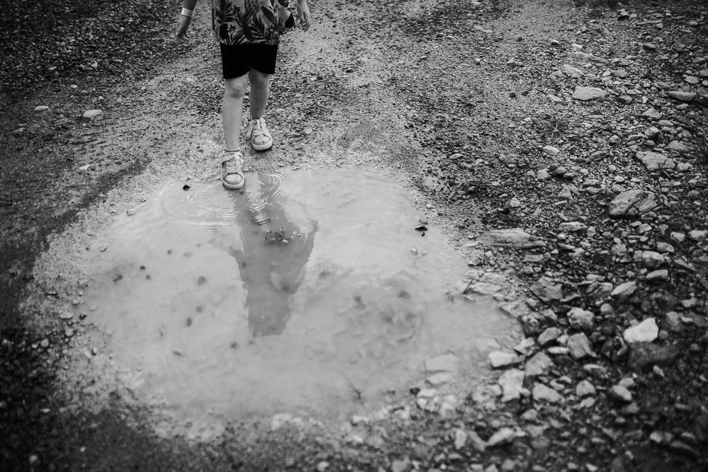 Black and white girl stepping into the edge of a big puddle with her reflection in the puddle
