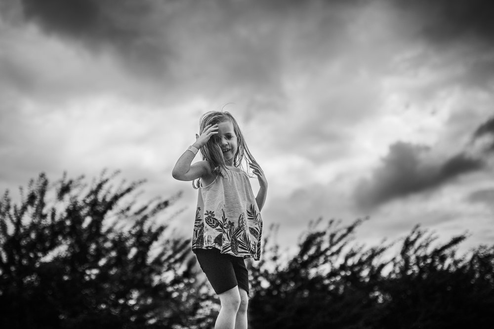 Black and white; girl laughing and pulling the hair from her face against a dramatic cloudy sky