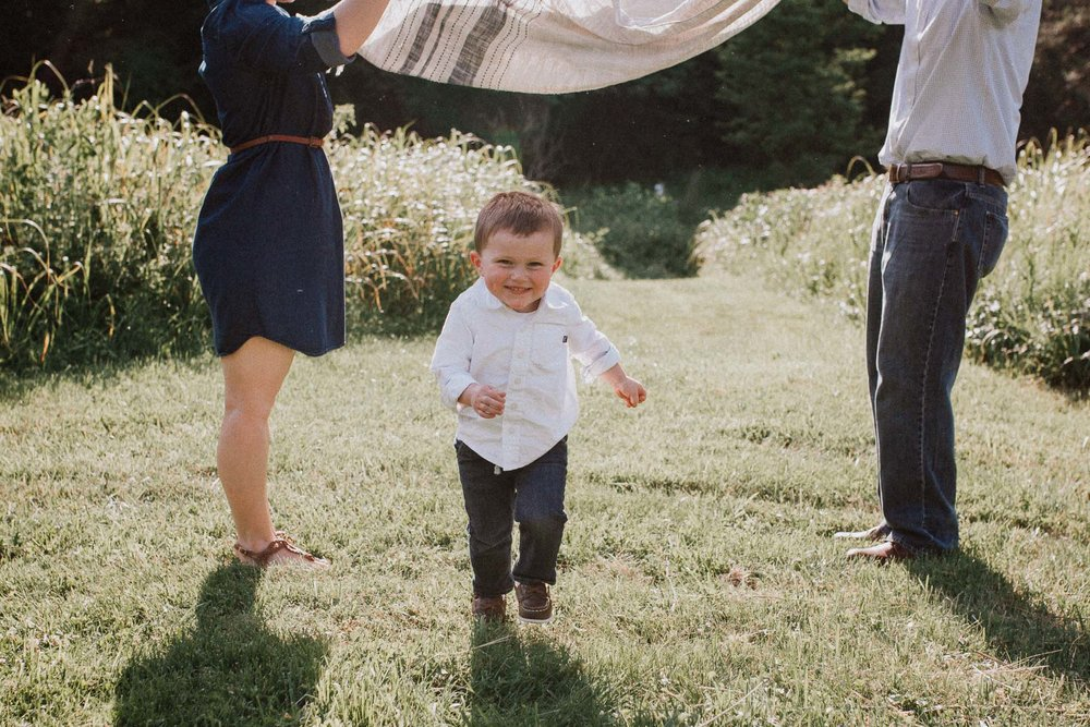 Little boy running under a blanket being held by his parents at Cabell's Mill in Chantilly, Virginia