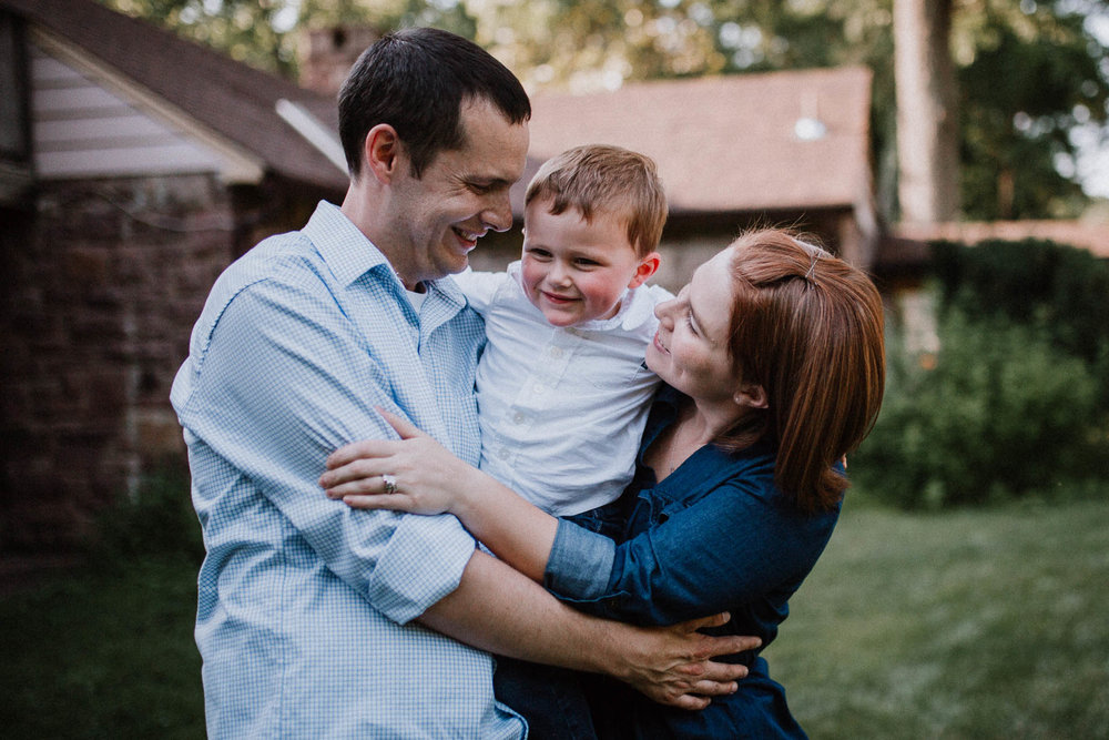 Family of three squish together, hug, and laugh at Cabell's Mill in Chantilly, Virginia