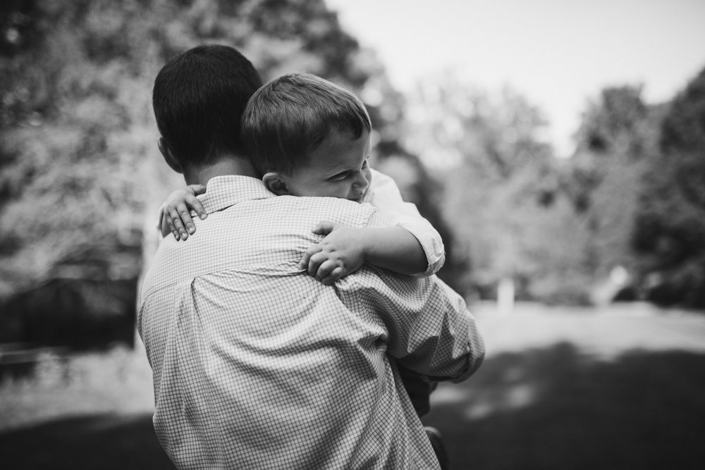 Black and white; toddler hugging his dad tight at Cabell's Mill in Chantilly, Virginia