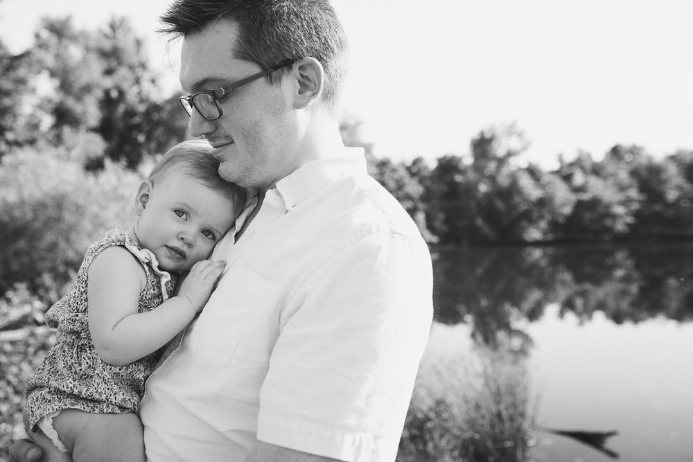 black and white; baby girl leans her head on her dad's chest at Claude Moore Park in Sterling, VA
