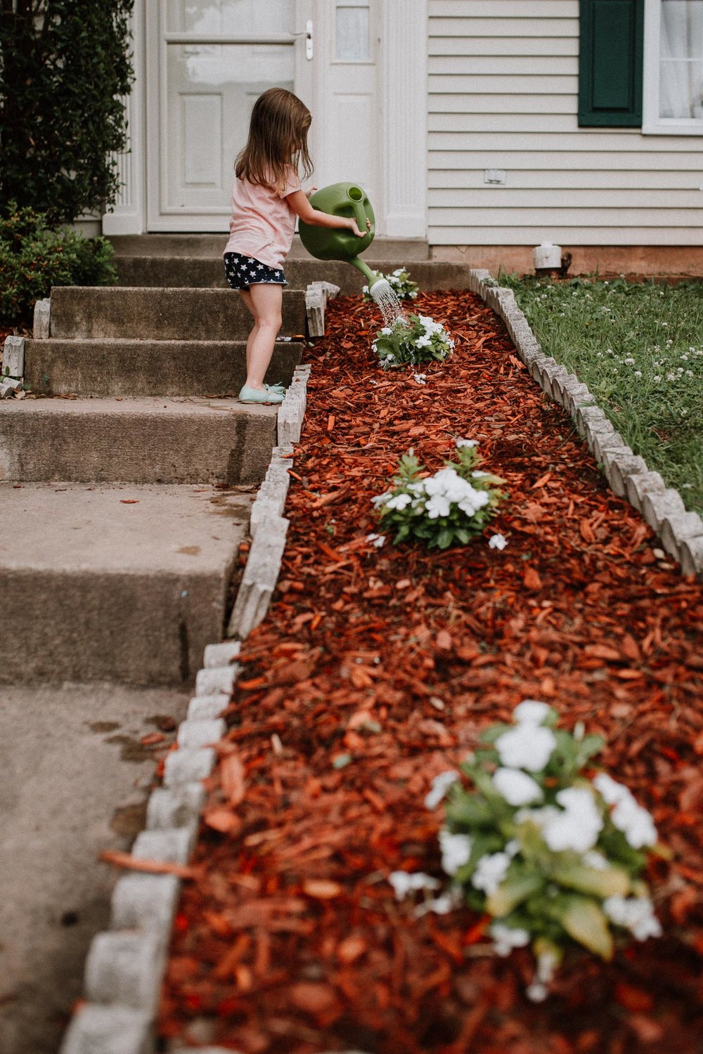 Lifestyle Photography; toddler watering flowers outside in Ashburn, Virignia
