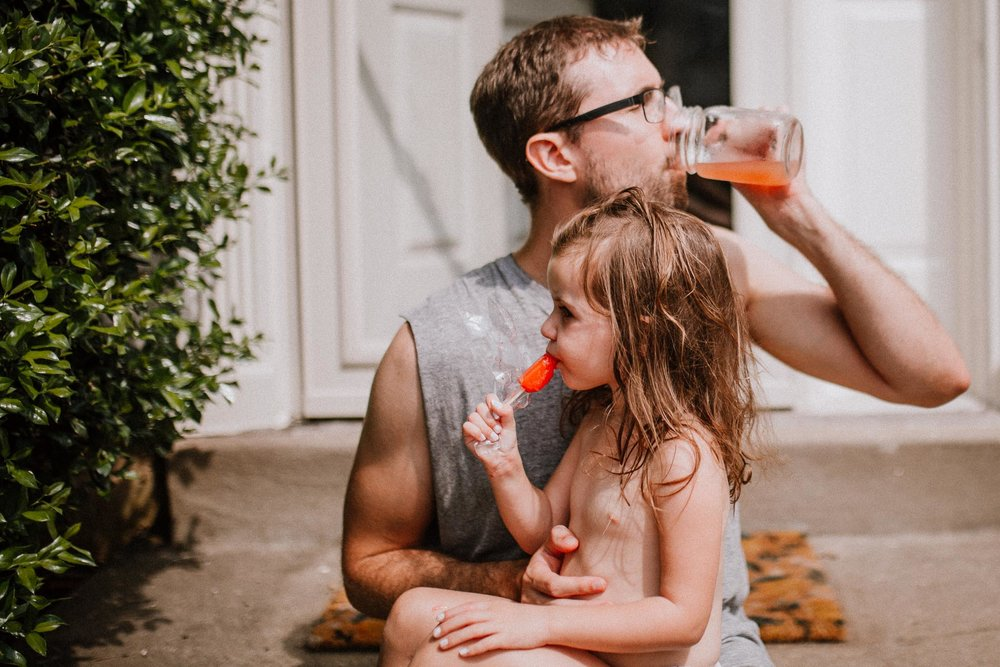Toddler sitting on dad's lap eating a popsicle while dad takes a drinks