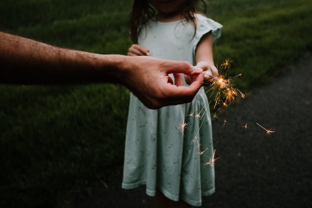 Dad handing toddler in a blue dress a sparkler on the Fourth of July
