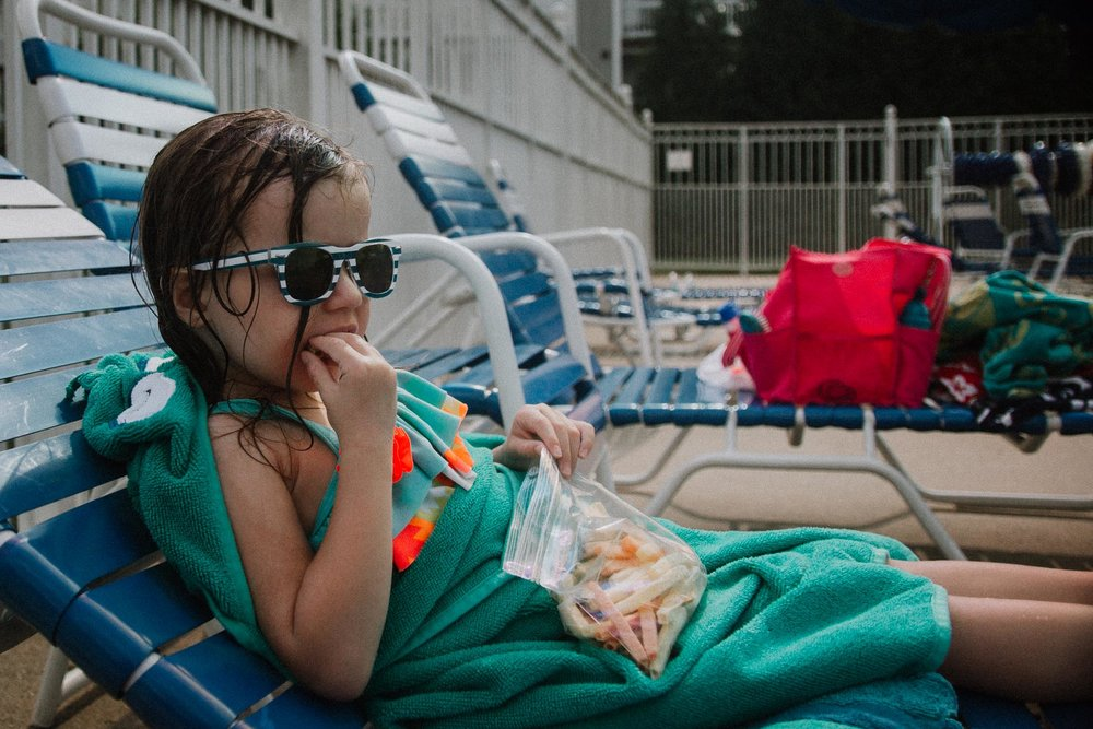 Toddler in sunglasses and a towel sits on a beach chair at the pool eating a snack